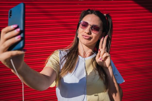 재미 있고 귀여운 소녀가 셀카를 찍고 평화 사인을하는 두 손가락을 보여줍니다.
