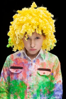 노란 광대 가발과 화려한 옷을 입고 슬픈 얼굴을 한 재미있는 소년.