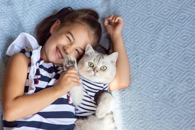 Смешная брюнетка девушка лежит с кошкой