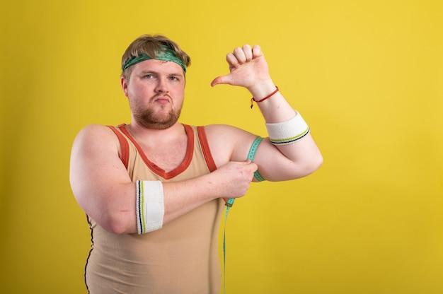 운동복을 입은 재미 있고 쾌활한 뚱뚱한 남자가 팔을 측정합니다. 과체중 남자는 스포츠에 들어갑니다. 노란색 배경 분리. 고품질 사진