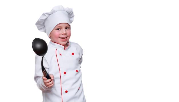 キャップをかぶった料理人の形をしたおかしな子供がおたまを持って面白く微笑む