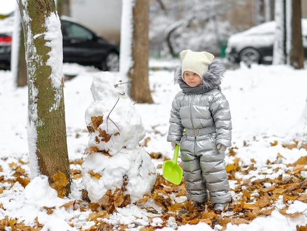 Забавная девочка в серебряном комбинезоне держит игрушечную лопату и лепит снеговика