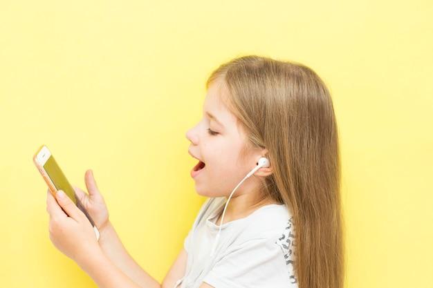 Смешная маленькая девочка с длинными волосами на желтом фоне держит в руках смартфон с наушниками и улыбается. понятие о детях и гаджетах, социальных сетях, тик-токе.