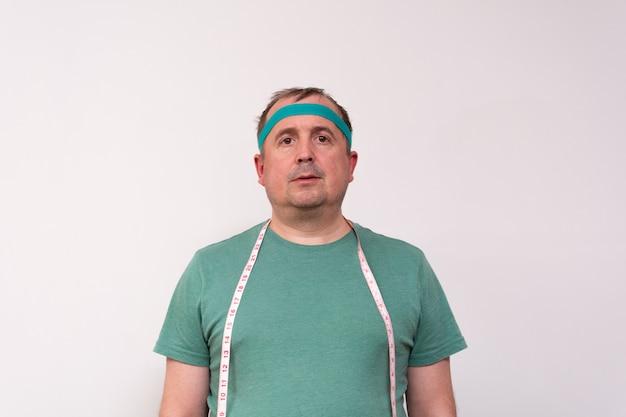 Забавный человек в зеленой бандане и футболке с рулеткой на шее
