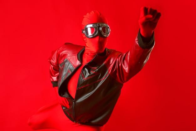 Забавный супергерой в красном купальнике и защитных очках летит вперед