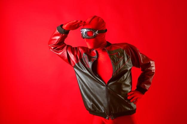 빨간 레오타드와 보호 안경을 쓴 재미있는 슈퍼 히어로가 앞을 내다본다