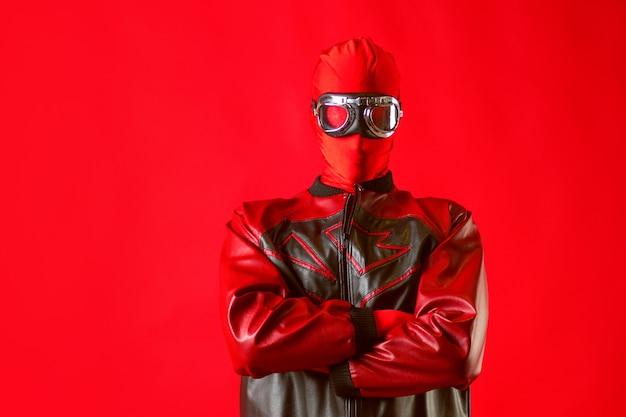 Забавный супергерой в красном купальнике и защитных очках. человек в красном на красной стене