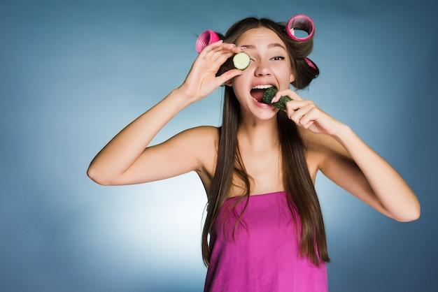 Веселая юная девушка хочет быть красивой, на голове бигуди держит огурец для увлажнения кожи лица