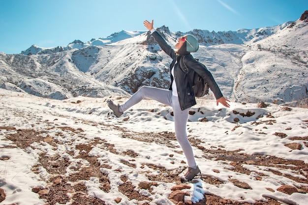 안경을 쓴 재미있는 젊은 여성이 눈 위를 여행합니다. 겨울 시즌에 산 봉우리입니다.