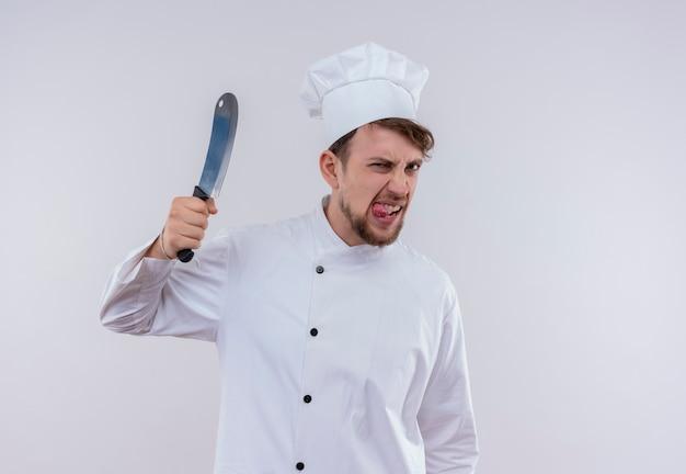 白い壁を見ながら肉切り包丁を保持している白い制服を着た猛烈な若いひげを生やしたシェフの男