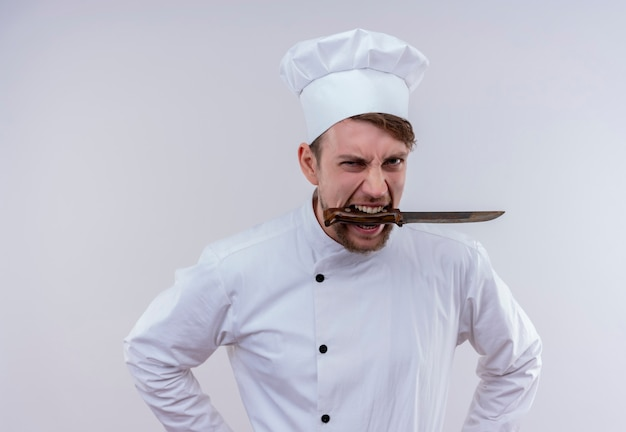 白い壁を見ながら彼の口に白い炊飯器の制服と帽子保持ナイフを身に着けている猛烈な若いひげを生やしたシェフの男