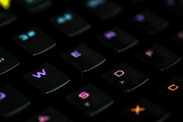 Rgbカラーのバックライトを備えたゲーミングキーボードは、テキスト用のスペースがある黒い壁にクローズアップを撮影しました。ゲーム、eスポーツ、ゲーマーのワークスペースのコンセプト。平面図、マクロ。デスクトップの壁紙。