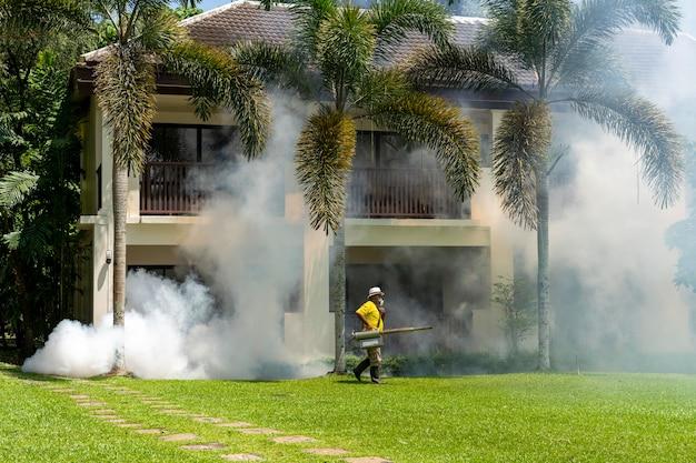 Садовник отравляет насекомыми, распыляя инсектицид или пестициды для борьбы с насекомыми в отеле
