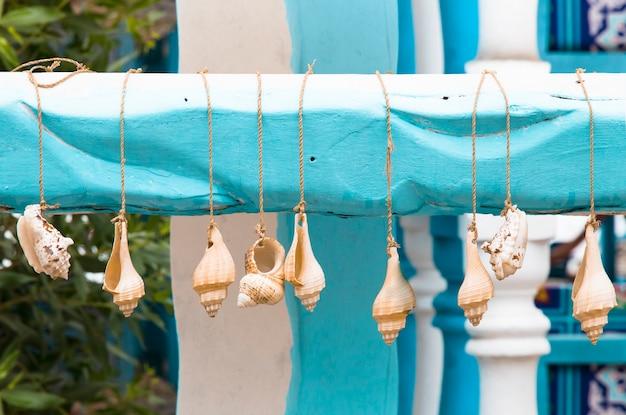 바다 근처 열대 정원에 있는 카페의 여름 테라스 장식에 있는 조개 화환