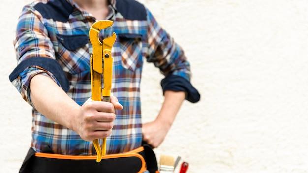 Газовый ключ в руках рабочего в синей клетчатой рубашке. скопируйте пространство.