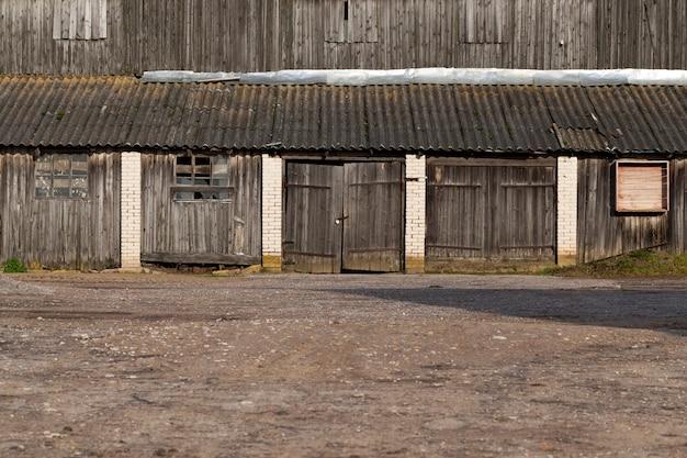 Общий план старого заброшенного здания с запертыми воротами из деревянных досок