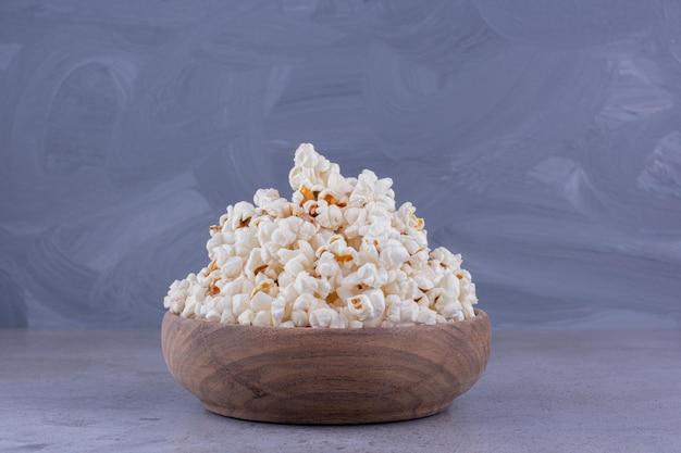 Щедрая порция свежеприготовленного попкорна в деревянной миске на мраморном фоне. фото высокого качества