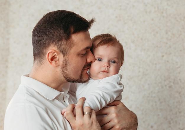 明るい表面に若い父と赤ん坊の娘の優しい肖像画。優しさ、親子関係