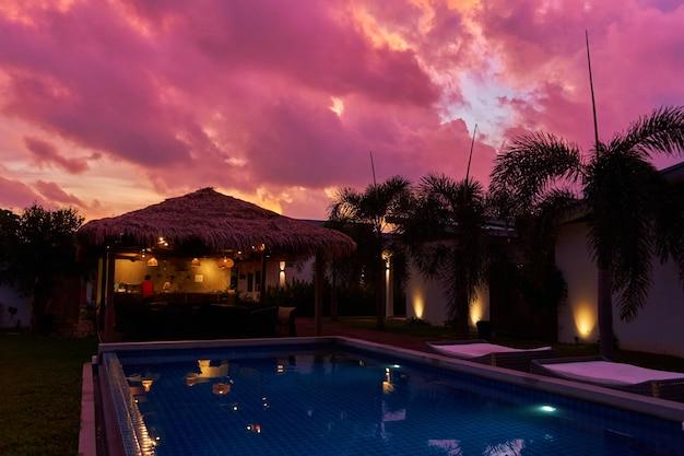 茅葺きのバンガローにそびえる穏やかな夕焼け空。熱帯地方のエキゾチックなリゾート