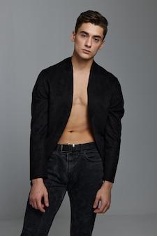 裸の胴体にボタンを外したジャケットを着て、灰色のスペースにズボンをはいた紳士。