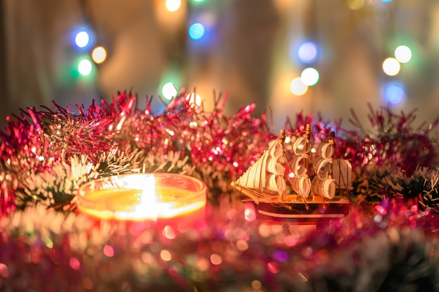 きらめく花輪を背景に見掛け倒しに囲まれたギフトボートとお正月キャンドル。