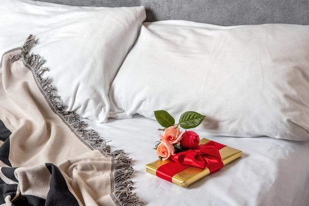 Подарочная коробка и цветы лежат в постели рано утром. контент для молодоженов и влюбленных на день всех влюбленных.