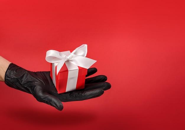 Подарочная коробка, украшенная бантом, лежит на ладони в черной защитной перчатке.