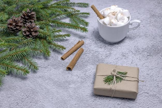 クラフト紙で作られたギフトボックスマシュマロシナモンスティックとモミの枝が付いたココアのカップ