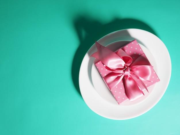 Подарочная коробка с розовой лентой лежит на тарелках-блюдцах на мятном фоне.