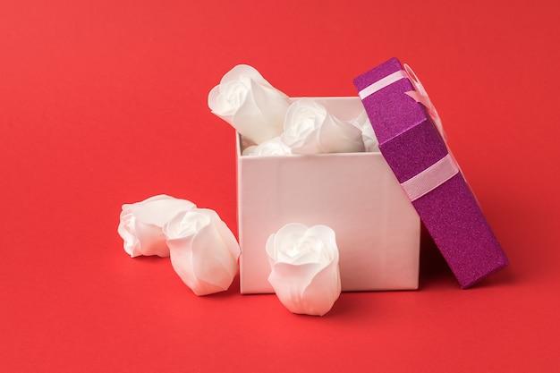 붉은 벽에 흰 장미 꽃 봉 오리와 선물 상자. 사랑의 개념.