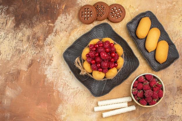 混合色のテーブルの上の茶色のプレートフルーツのギフトケーキとビスケット