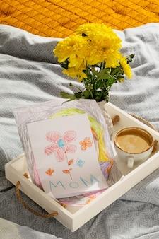 母の日のための子供からの贈り物写真からのカードと朝のベッドでのコーヒー