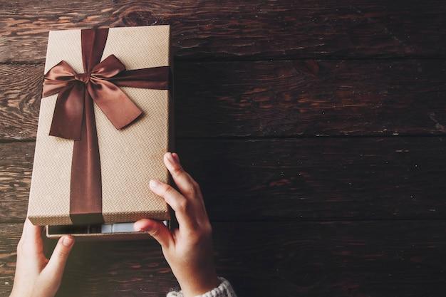Подарок в ваших руках на деревянном фоне
