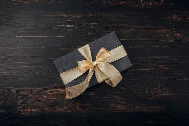 黒い紙で包まれ、金のリボンで結ばれたギフト