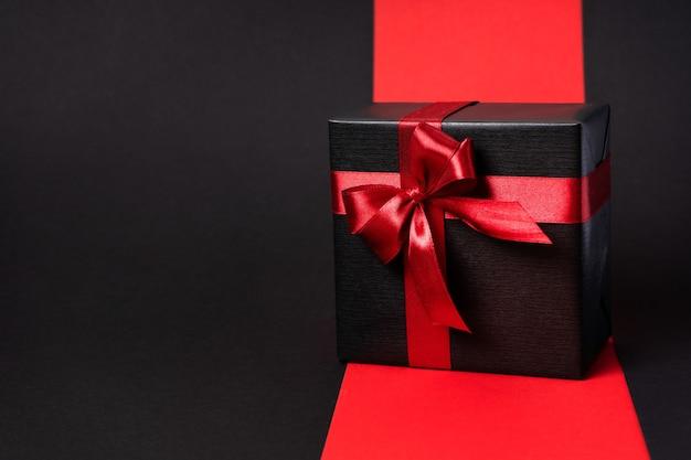 Подарок, завернутый в темную черную бумагу с роскошным бантом на ровном фоне. с местом для текста