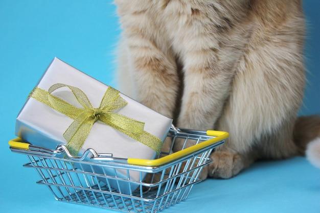 금속 쇼핑 바구니에 금색 활과 은색 종이로 싸인 선물. 빨간 고양이