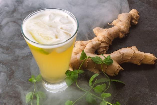 黒い大理石の背景に生姜ビールをグラスに乗せた生姜の根と、新鮮なミントと煙が雰囲気を作り出しています。