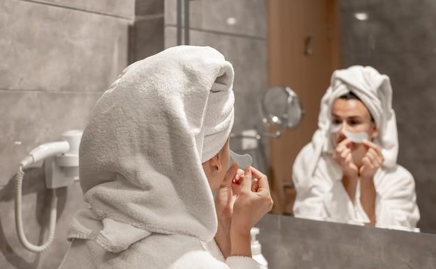 Девушка в халате и с полотенцем на голове наклеивает лоскутки под глаза в ванной перед зеркалом.
