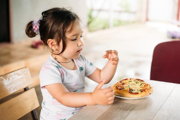 Девочка, ребенок на улице ест мини пиццу очень аппетитно