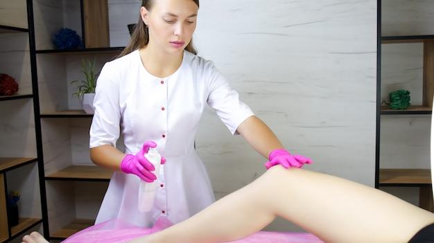 Девушка, мастер сахарной эпиляции, одной рукой держит колено модели, а другой сбрызгивает спрей, чтобы очистить его.