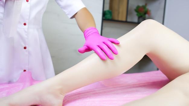 Девушка, мастер сахарной эпиляции, брызгает спреем на ногу модели и растирает ее рукой.