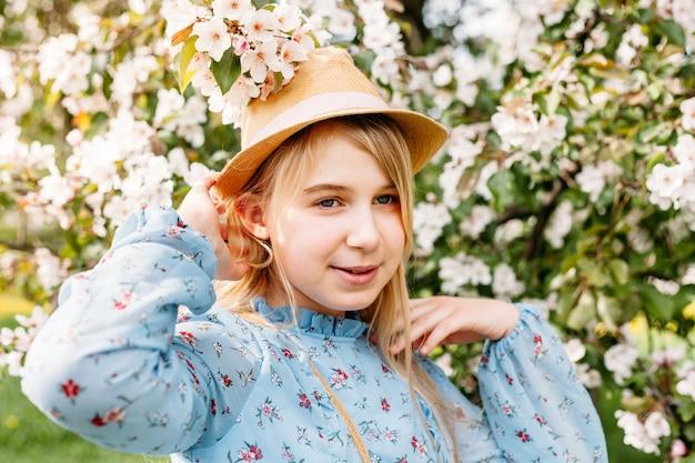 Девушка, подросток в шляпе гуляет весной по городу, цветущие деревья, яблоня
