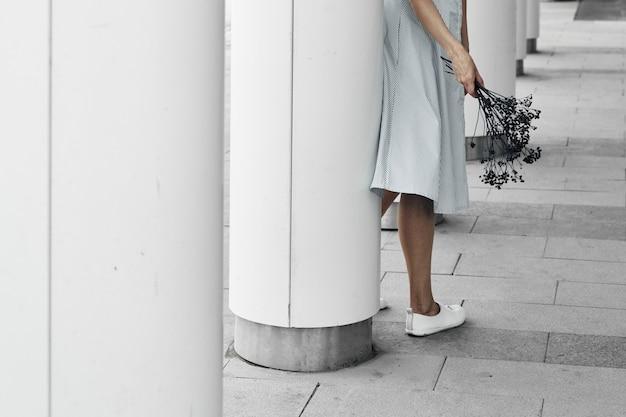 丸い白い柱を背景にした女の子が手に枝を持っています。建物の幾何学、街歩き。スペースをコピーします。