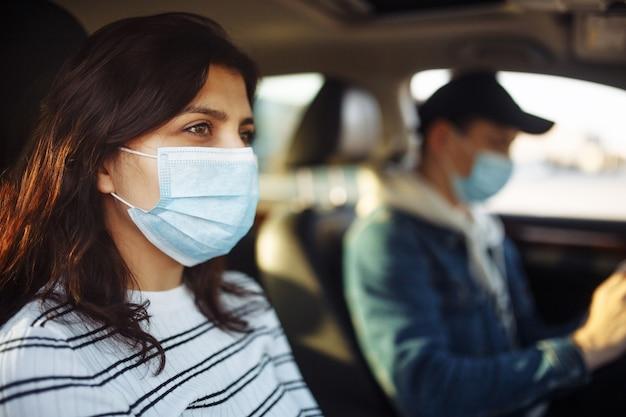 医療用マスクを着用してコロナウイルス検疫中に車で運転している女の子と男の子