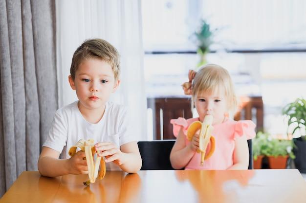 Девушка и мальчик едят банан.