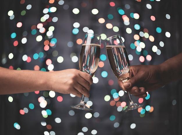 Девушка и парень спариваются с бокалами шампанского на красивых праздничных огнях боке