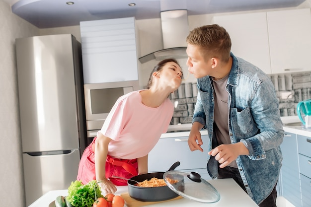 Девушка и парень вместе готовят ужин на кухне