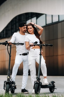 Девушка и парень гуляют на электросамокатах по городу, влюбленная пара на скутерах.