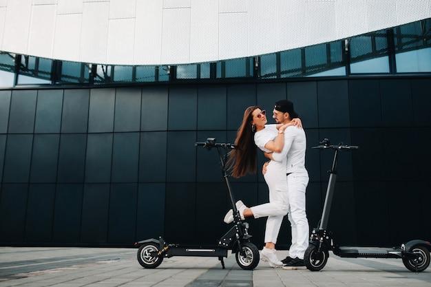 Девушка и парень гуляют на электросамокатах по городу, влюбленная пара на самокатах