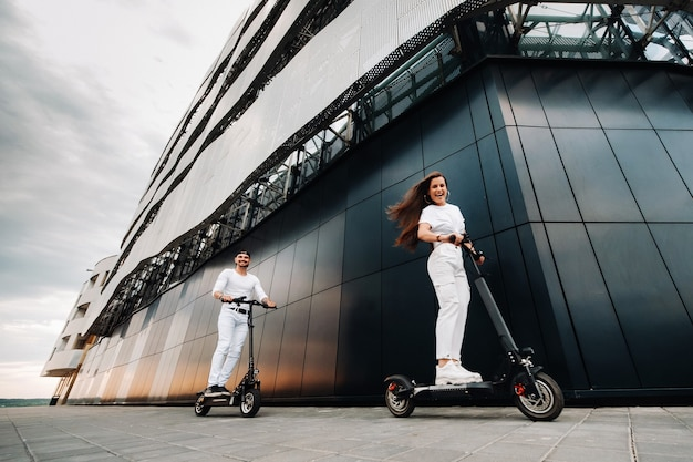 女の子と男が街中の電動スクーターを歩いている、カップルはスクーターに恋をしている